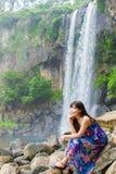 长的头发女孩在瀑布附近坐 库存图片