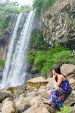 长的头发女孩在瀑布附近坐 免版税库存照片