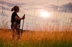 长的头发女孩通过草甸走在惊人的金黄日落背景 免版税库存照片