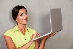 长的头发女性举行的膝上型计算机和微笑 图库摄影