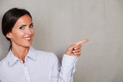 长的头发女性指向她的左边 免版税图库摄影