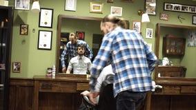 长的头发理发师对理发做年轻有胡子的人在理发店 4K 股票录像