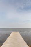 长的水泥桥梁延伸到有自然海景后面的海 免版税库存照片