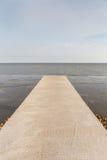长的水泥桥梁延伸到有自然海景后面的海 库存照片