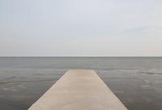 长的水泥桥梁延伸到有自然海景后面的海 图库摄影