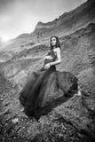 长的黑礼服的妇女在沙子峡谷 库存照片