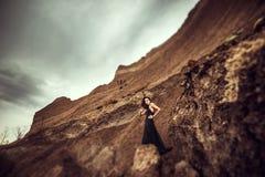 长的黑礼服的妇女在沙子峡谷 免版税库存照片