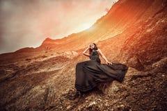 长的黑礼服的妇女在沙子峡谷 图库摄影
