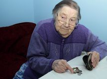 年长祖母在桌上认为便士 免版税库存照片