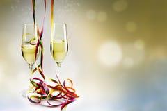 长笛香槟玻璃和五颜六色的飘带反对bokeh 免版税库存照片