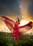 长红色礼服摆在的时兴的美丽的少妇室外与多云剧烈的天空在背景中 可爱的浅黑肤色的男人 免版税库存图片