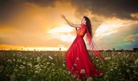 长红色礼服摆在的时兴的美丽的少妇室外与多云剧烈的天空在背景中 可爱的浅黑肤色的男人 免版税图库摄影