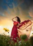 长红色礼服摆在的时兴的美丽的少妇室外与多云剧烈的天空在背景中 可爱的浅黑肤色的男人 免版税库存照片