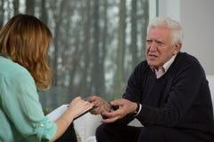 年长耐心谈话与心理治疗家 免版税库存图片