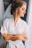 长袍和面纱微笑的摆在的美丽的白肤金发的新娘在窗口,婚姻的准备附近 免版税库存照片