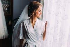 长袍微笑的摆在的美丽的白肤金发的新娘在窗口,婚姻的准备附近 库存照片