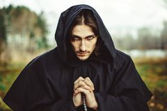 长袍的一名修士祈祷在森林的 免版税图库摄影