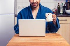 长袍的食用的人检查电子邮件和咖啡 免版税库存图片