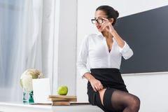 长袜的年轻性感的老师坐书桌 免版税图库摄影