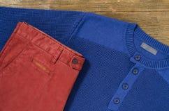 长裤和毛线衣在木桌上 库存照片