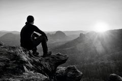 黑长裤的疲乏的成人远足者,夹克和黑暗的盖帽坐峭壁边缘和看对在谷轰鸣声的五颜六色的薄雾 免版税图库摄影
