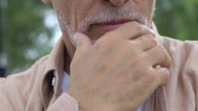长辈在公园起了皱纹坐长凳和急切地接触灰色胡子的人 影视素材