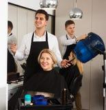 年长金发碧眼的女人的专业美发师切口头发沙龙的 免版税图库摄影