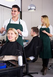 年长金发碧眼的女人的专业美发师切口头发 库存照片
