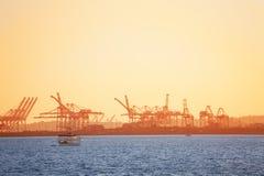 长滩与起重机的航运港在日落 库存图片