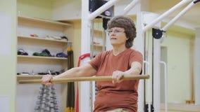 延长年长的妇女,做物理疗法行使用棍子在健身屋子里 健康体操 活动家 股票录像