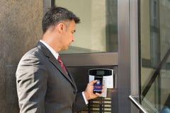 门商人解除武装的保安系统与智能手机的 免版税库存照片