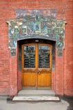 门在用瓦片装饰的老砖房子里 库存图片