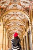 门廓在波隆纳,红色贝雷帽的女孩站立  免版税图库摄影