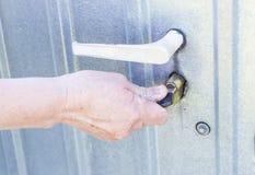 门把手和固定锁,有女性手打开的铁门的 图库摄影