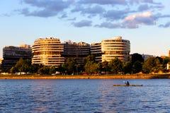 水门旅馆和公寓在与一艘皮船的金黄小时在Th 免版税图库摄影