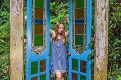 门的少妇在一个热带庭院里 图库摄影