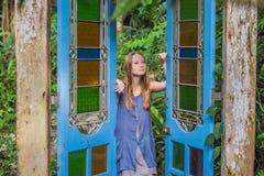 门的少妇在一个热带庭院里 库存照片