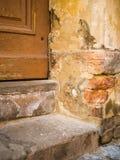 门老木 Weathered崩裂了在一个古老石房子的墙壁的油漆那么老木门 一个老石墙与 图库摄影