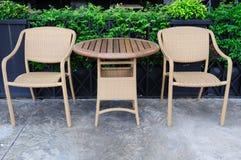 门被设置的藤条桌和椅子。 图库摄影