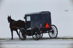 门诺派中的严紧派的儿童车游遍雪 免版税库存图片