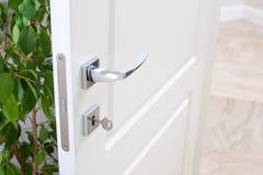 门配件特写镜头  与现代镀铬物把柄的一个白色门,有钥匙的门锁 免版税库存照片
