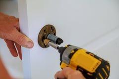 门锁的设施使用一把螺丝刀的 锁设施的木匠有电钻的到木门里 库存照片