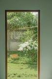 门以开放对庭院的看法有绿色花树的 库存照片