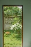 门以开放对庭院的看法有绿色花树的 免版税库存图片