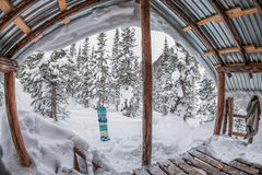 门廊房子,瑞士山中的牧人小屋在有雪的冬天森林里在山和 库存图片