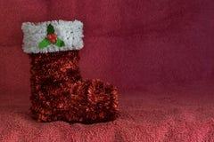 闪亮金属片圣诞节在红色背景的长袜装饰品 库存图片