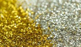 从闪亮金属片的金黄和银色背景与bokeh 库存图片