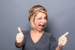 闪光和微笑为凉快的态度的挥动的少妇 免版税库存照片