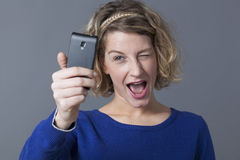 闪光和笑为她的与手机的selfie的乐趣年轻白肤金发的妇女 免版税库存照片