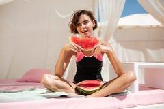 闪光时髦的泳装的美丽的女孩坐在海滩帐篷和,当看在与时西瓜切片的照相机 免版税库存图片